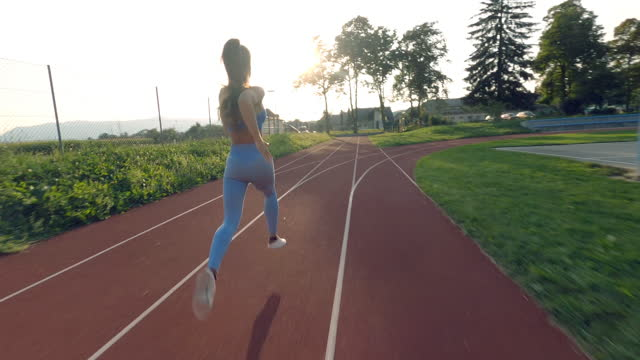 DRONE SLO MO Athletic young woman running on a running track