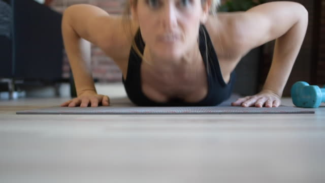vídeos de stock e filmes b-roll de athletic young woman with blond hair and blue eyes with a beautiful look, she trains at home because of the isolation for covid19, and makes the burpees,  and jump high. - treino em casa