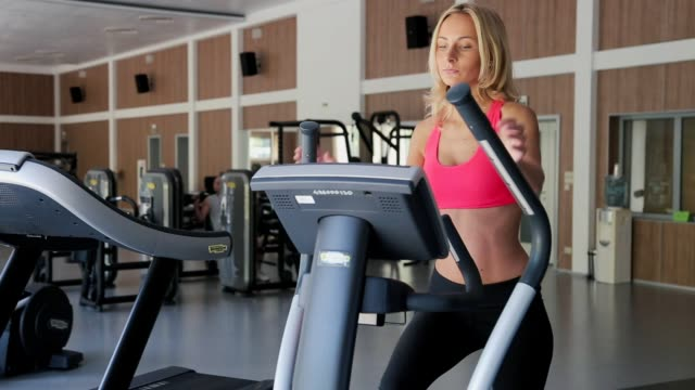 Athletic young woman working out on stepper machine at the gym, fitness club video
