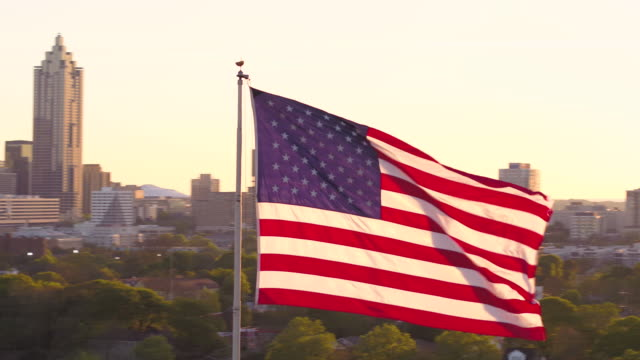 Atlanta Aerial v266 Flying low closeup around American flag with full cityscape views at sunset