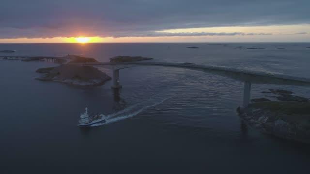atlantic ocean road in norway at sunset. ship is passing under storseisundet bridge. aerial view - oceano atlantico video stock e b–roll