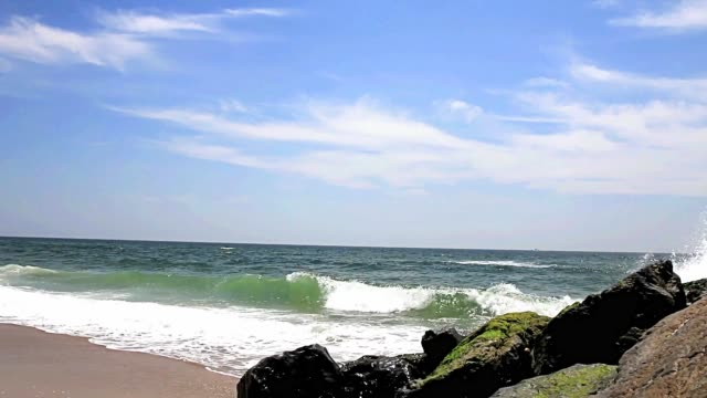 Atlantic Ocean waves rolling on the shore next to a large rock jetty off of Fire Island New York Side View of the Atlantic Ocean beach next to a large rock jetty on Fire Island New York. jetty stock videos & royalty-free footage