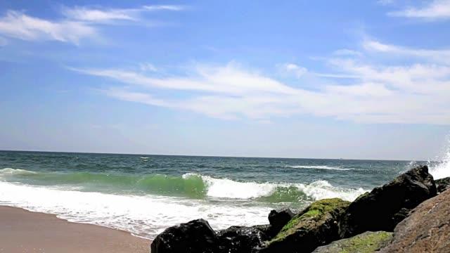 atlantic ocean dalgaları fire island new york açıklarında büyük bir kaya iskelesi yanında kıyıda haddeleme - dalgakıran stok videoları ve detay görüntü çekimi