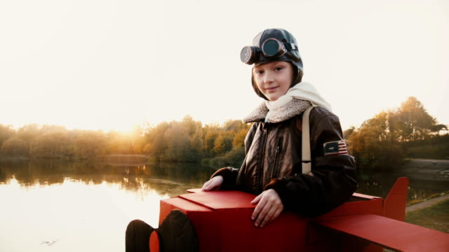 Atmospheric portrait shot of cute girl in fun retro plane pilot costume looking at camera with calm eyes slow motion.