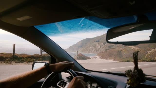 vídeos de stock e filmes b-roll de atmospheric pov shot of man driving along incredible sunny ocean coast road with mountain view at big sur california. - big sur
