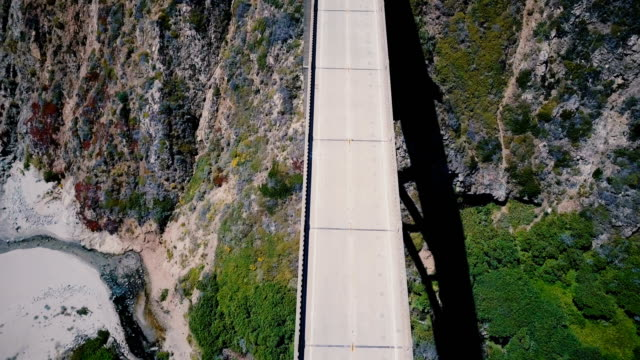 vídeos de stock e filmes b-roll de atmospheric top view aerial shot of famous bixby creek bridge with no traffic on highway 1, iconic landmark in big sur. - big sur