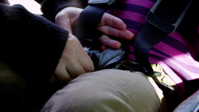 Attaching car seat buckle, closeup video