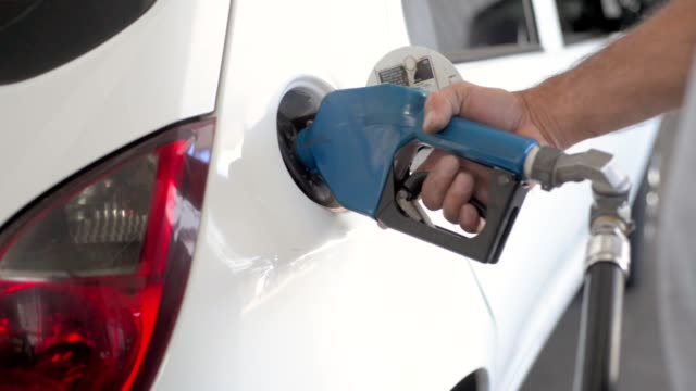 Attendant from gas station refueling a car Attendant from gas station refueling a car refueling stock videos & royalty-free footage