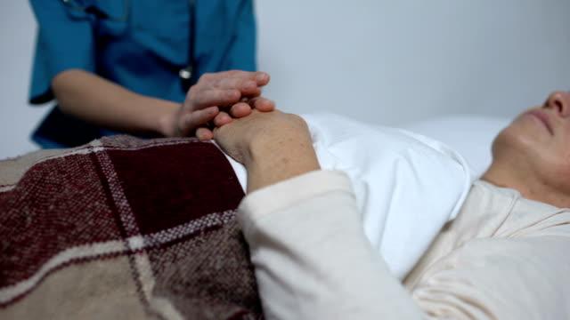 女性患者の手をなでる主治医、彼女を支える、ホスピス ビデオ