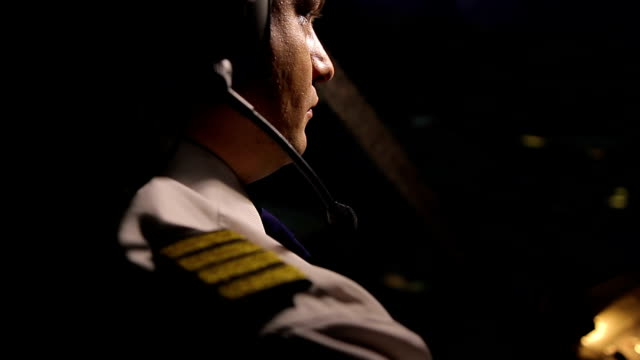 Attentive captain pilot in headset navigating huge airliner at night, job duties Attentive captain pilot in headset navigating huge airliner at night, job duties cockpit stock videos & royalty-free footage