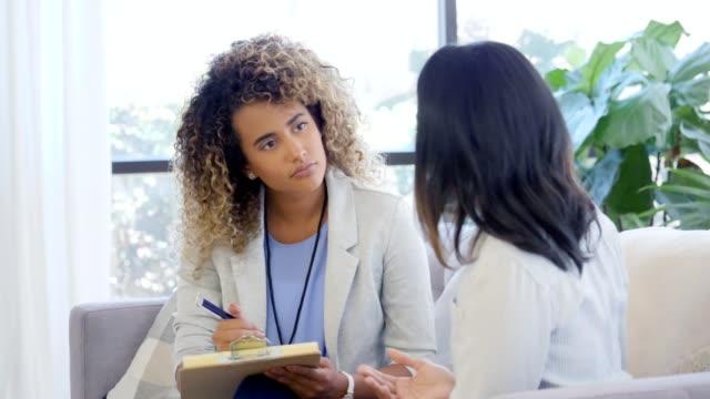 attentive counselor listens to female patient - therapist filmów i materiałów b-roll