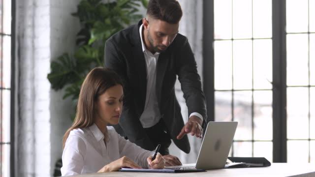 aufmerksamer mitarbeiter hört dem vorgesetzten zu und schreibt notizen. - unterordnung stock-videos und b-roll-filmmaterial