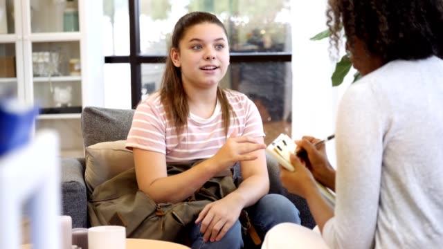 vídeos y material grabado en eventos de stock de profesional de salud mental mujer atenta toma notas mientras escucha al paciente adolescente - profesional de salud mental