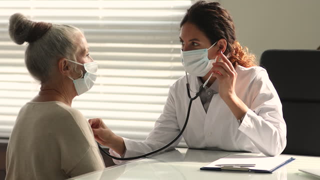 Attentive professional female cardiologist checking heart of old patient. Attentive professional female cardiologist in protective facemask checking heartbeat of elderly mature female patient. Old senior woman in respirator visiting doctor, complaining about bronchitis. cardiologist stock videos & royalty-free footage