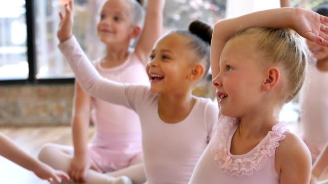 Attentive young ballerinas answer ballet teacher's questions before class Cute elementary and preschool age ballerinas raise their hands to answer their ballet teacher's questions. They are sitting on the floor in the ballet studio. The teacher is asking them questions before class begins. dance studio stock videos & royalty-free footage