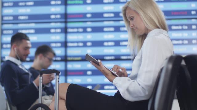 Séduisante femme d'affaires adultes aide ordinateur tablette tout en attente d'embarquement à la salle d'embarquement à l'aéroport. - Vidéo