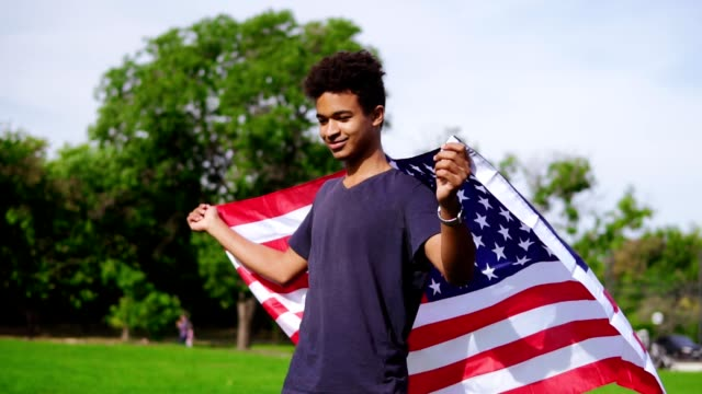 Attractive african american man holding American flag in his hands on the back standing in the green field then raising it up and waving in the wind. Patriotic concept video