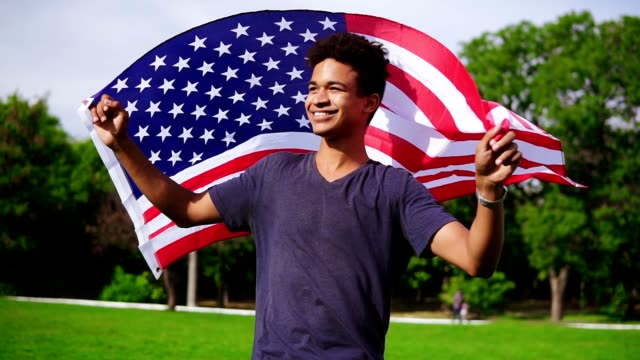 vídeos de stock e filmes b-roll de attractive african american man holding american flag in his hands on the back walking in the green field and smiling proudly. patriotic concept - afro americano