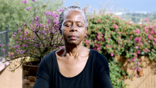 attractive african american senior woman meditating outdoors - posizione corretta video stock e b–roll