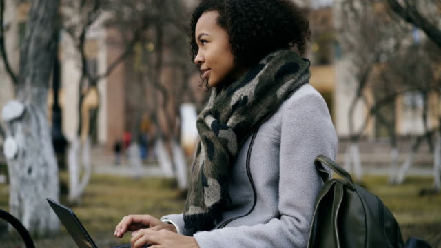 Attractive african american student girl typing on laptop computer sitting on bench near univercity video