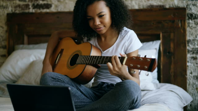 attractive african american teenager girl concentraing learning to play guitar using laptop computer sitting on bed at home - гитара стоковые видео и кадры b-roll