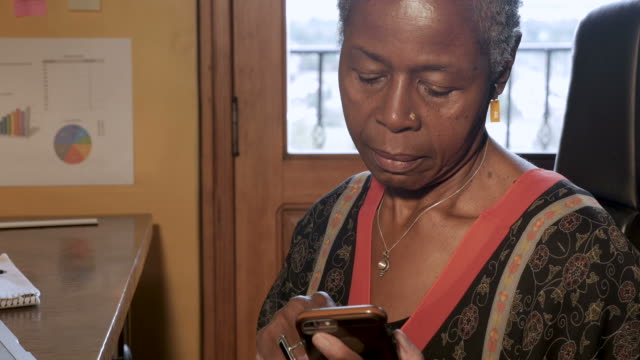 Attractive African American woman using her smart phone technology app video