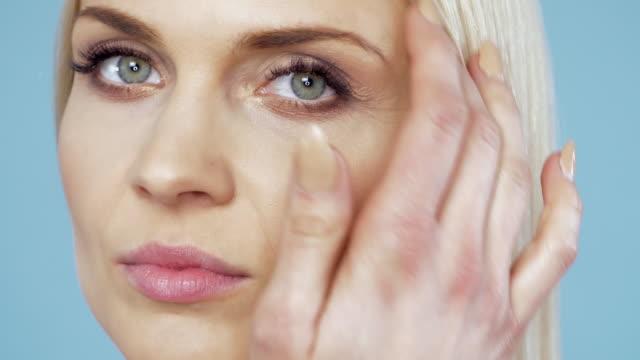魅力的で大人の女性が彼女の顔に触れる - スキンケア点の映像素材/bロール
