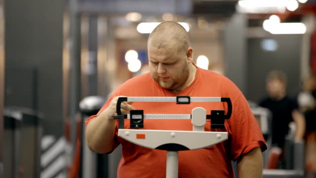 Attractive and overweight man standing on a mechanical scale