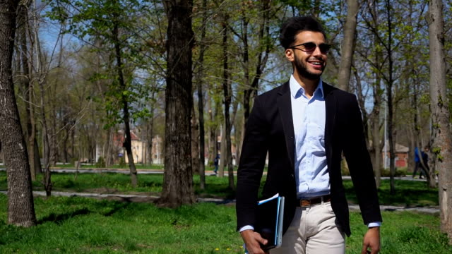 Attractive Arabian guy walking in park with documents and laptop in hand video