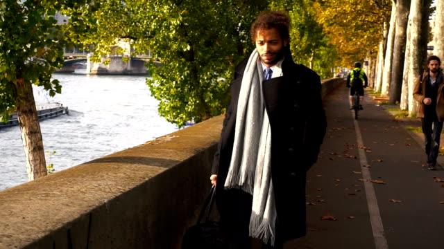 Attractive Arabian journalist walking near Seine in slow motion video