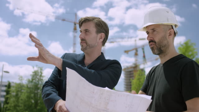 attractive architect and construction manager discussing constructions plans outside at the building lot - construction worker stock videos and b-roll footage