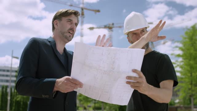 外の建設計画を議論する魅力的な建築家および建設マネージャー - プロジェクトマネージャー点の映像素材/bロール