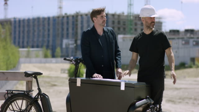 Attractive Architect and construction worker discussing building plans video