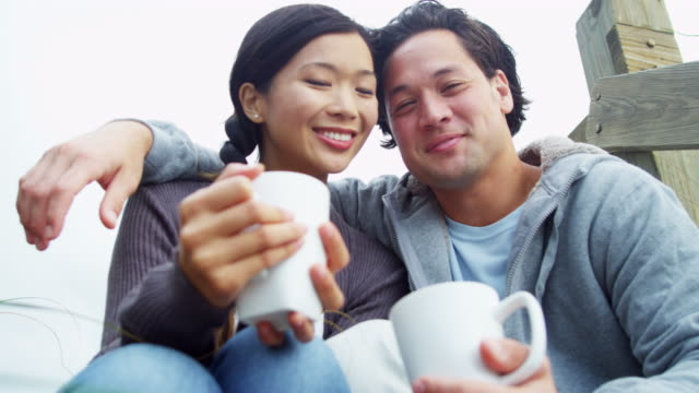 vidéos et rushes de chinois asiatiques attrayants couple buvant café automne beach - évasion du réel