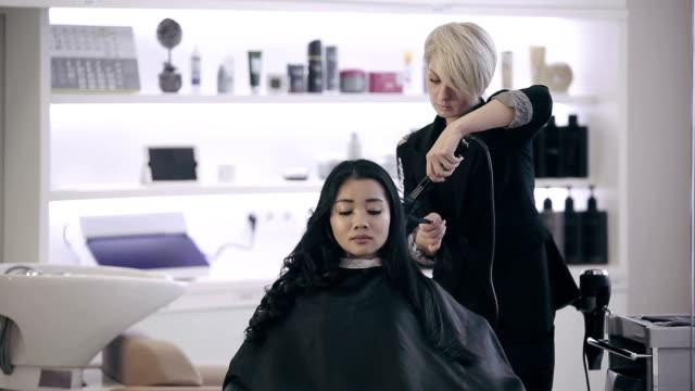 vidéos et rushes de jolie asiatique fille ethnicy une procédure de de curling - salons et coiffeurs