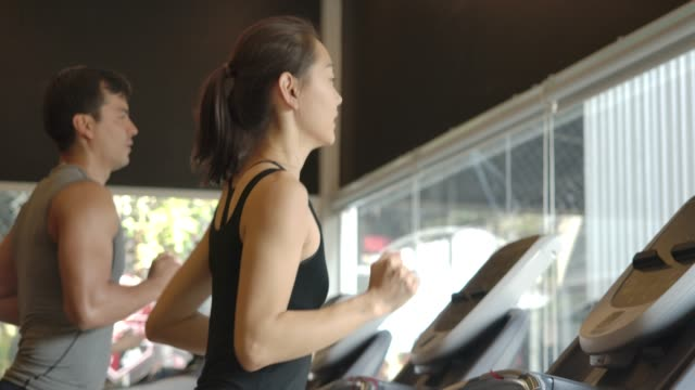 Attractive asian girl running on the treadmill in the sport gym. Slow Motion. Exercising, Women, Treadmill, Jogging, Cardiovascular Exercise health club stock videos & royalty-free footage