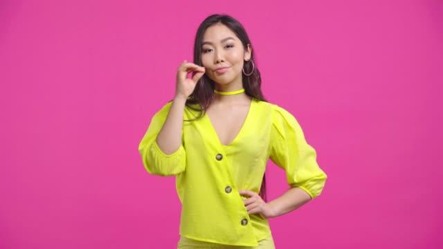 stockvideo's en b-roll-footage met aantrekkelijk aziatisch meisje dat mond die op roze wordt geïsoleerd - handen op de heupen