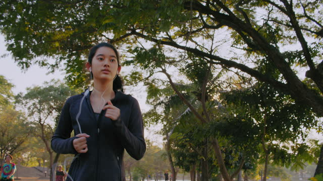 Attractive Asian Teenager girl listening music while running in the public park. Young woman jogging exercising in the morning.
