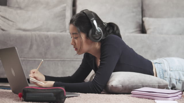 vídeos de stock e filmes b-roll de attractive asian teenager girl wearing headphone listening and studying online homeschool on tablet screen with her teacher and writing on notebook  coronavirus or covid 19 lockdown situation. video call technology with her advice to learn her homework. - isolado