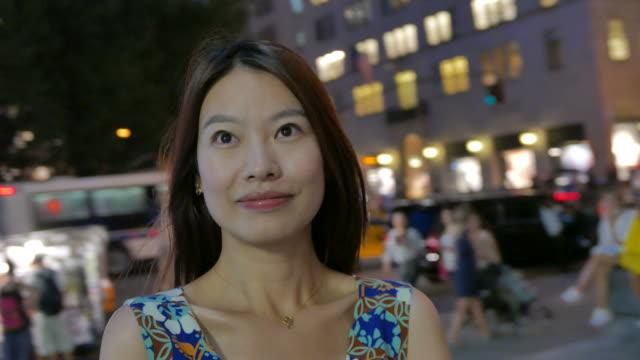 魅力的なアジアの女性は、市の日を楽しんでします。自由、インスピレーション、独立を象徴します。 - 米国旅行点の映像素材/bロール