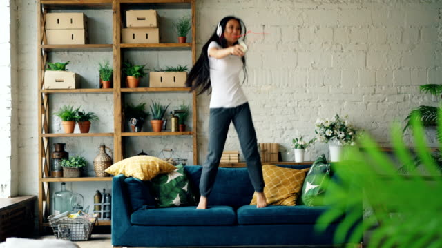 Attractive Asian woman is having fun at home listening to music through headphones holding smartphone, singing and dancing jumping on sofa. Modern technology and people concept.