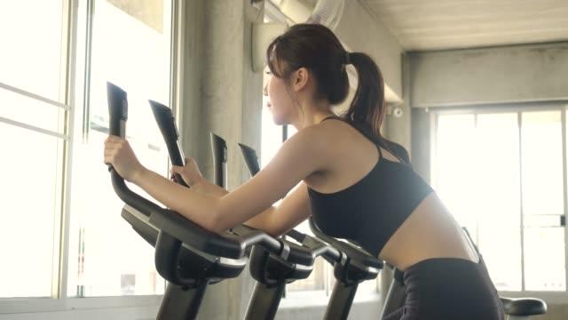ジムで回転している静止した自転車で魅力的なアジアの女性。スローモーション。ヘルスケア、運動とスポーツの概念。 - スポーツ用品点の映像素材/bロール