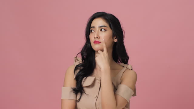 Attractive asian woman thought about question and found answer. Portrait of female posing at camera on pink background with copy space.
