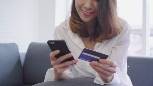 Attractive asian woman using credit card paying with mobile phone.