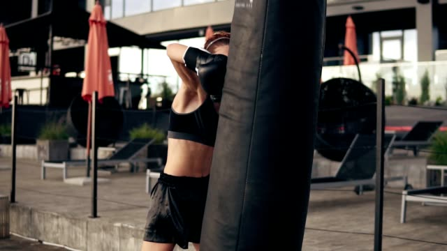 attractive athletic female boxer in gloves exercising with a bag. workout outside. female boxer training. self defence concept. slowmotion shot - kick boxing video stock e b–roll