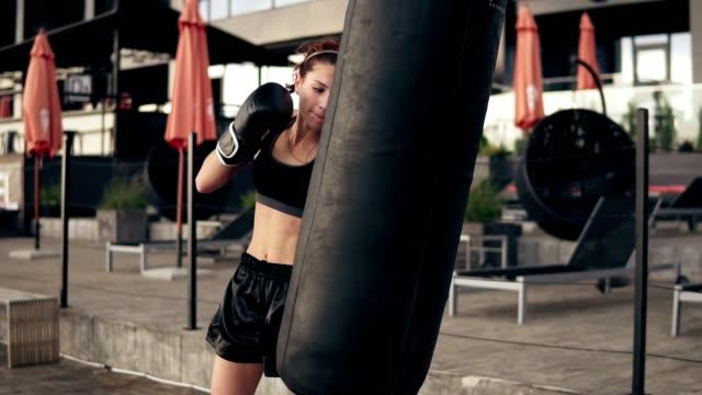 attraente pugile atletico con guanti che prendono a calci un sacco da boxe. allenati fuori. formazione boxer femminile. concetto di autodifesa - kick boxing video stock e b–roll