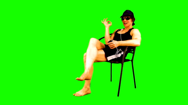 attraktiv atletisk kille sitter i en fåtölj, sola, titta i sin smartphone, lyssna på musik på den, njuter, drinkar från en flaska, ler och visar välkomst skyltar på chroma nyckel. - brunbränd bildbanksvideor och videomaterial från bakom kulisserna