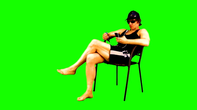 Attractive athletic guy is sitting in an armchair, sunbathing, looking in his smartphone, listening to music on it, enjoying and drinks from a bottle on chroma key.