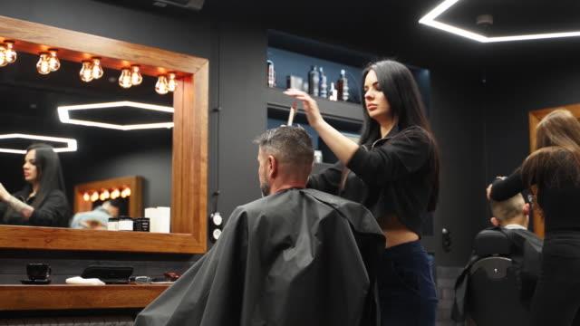 vidéos et rushes de fille de barbier attirante coupant le cheveu d'homme avec des ciseaux et le peigne. coupeur de cheveux féminin travaillant client de service. homme élégant s'asseyant dans la chaise de salon de barbier d'époque. femme de coiffeur faisant la coupe - coiffeur