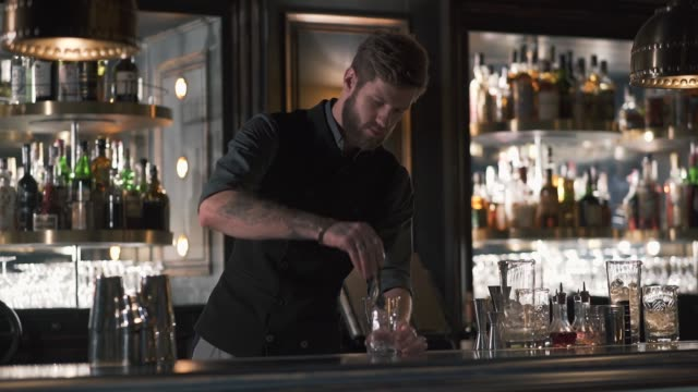Attractive barman mixologist adding big cube of ice making a cocktail in beautiful modern bar. video